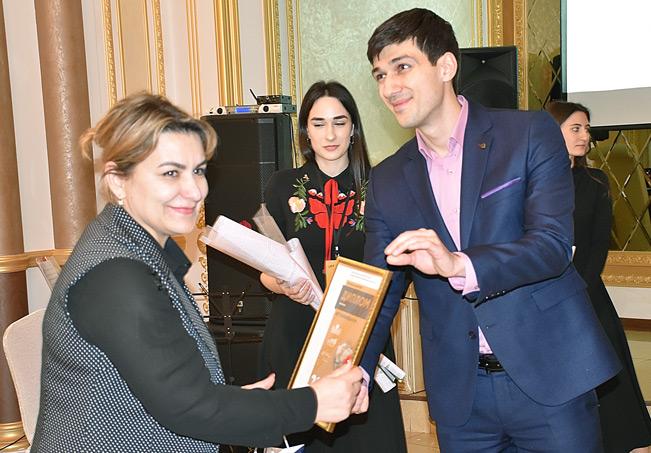 Директор центра «Мой бизнес» Артур Езаов награждает руководителя фабрики «IDEAL» Медину Тамбиеву